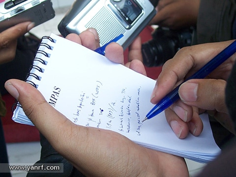 Journalist writing in a piece of paper